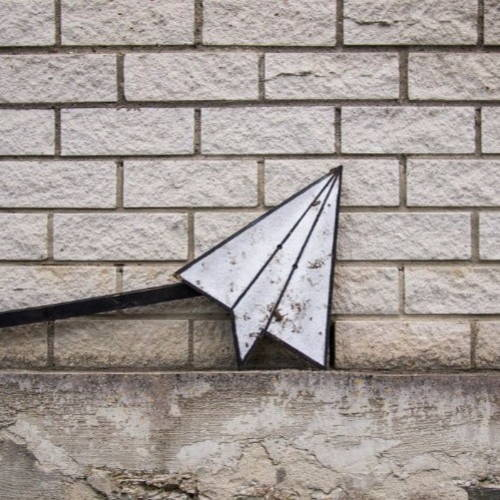 white paper plane leaning on the wall