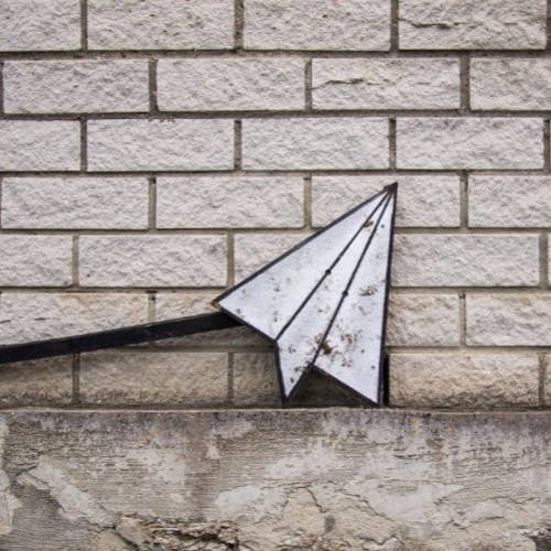 paperplane leaning towards the wall